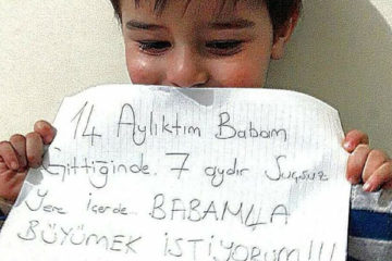 Children of jailed victims express their sorrow with messages on placards